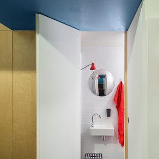 Aménagement d'une petit salle de bain contemporaine avec un lavabo suspendu, un carrelage blanc, un mur blanc et un sol noir.