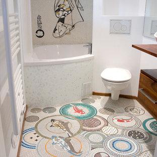 Ejemplo de cuarto de baño principal, asiático, pequeño, con armarios con paneles lisos, puertas de armario de madera oscura, encimera de madera, combinación de ducha y bañera, baldosas y/o azulejos multicolor, baldosas y/o azulejos de porcelana, paredes blancas, suelo con mosaicos de baldosas, sanitario de pared, lavabo sobreencimera y bañera esquinera