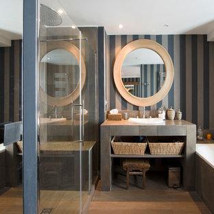 Idées déco pour une douche en alcôve principale contemporaine de taille moyenne avec une baignoire posée, un mur marron, un sol en bois brun et un lavabo intégré.