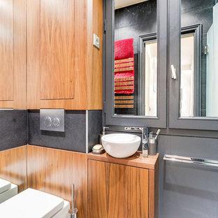 Esempio di una piccola stanza da bagno con doccia classica con ante a filo, ante in legno scuro, doccia a filo pavimento, WC sospeso, piastrelle nere, piastrelle in ardesia, pareti nere, pavimento in ardesia, lavabo da incasso e top in legno
