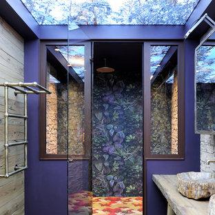 Cette photo montre une douche en alcôve principale éclectique avec un placard sans porte, des portes de placard en bois brun, un mur multicolore, une vasque, un plan de toilette en bois et une cabine de douche à porte battante.