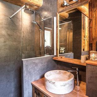 Cette image montre une petit salle de bain chalet en bois avec un placard à porte shaker, des portes de placard en bois brun, un carrelage gris, un mur marron, une vasque, un plan de toilette en bois, aucune cabine, un plan de toilette marron, meuble simple vasque, meuble-lavabo encastré et un plafond en bois.