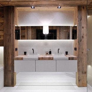 Diseño de cuarto de baño principal, rural, con armarios con paneles lisos, puertas de armario blancas, bañera encastrada sin remate, ducha esquinera, paredes beige, lavabo bajoencimera, encimera de madera, baldosas y/o azulejos blancos y ducha con puerta con bisagras
