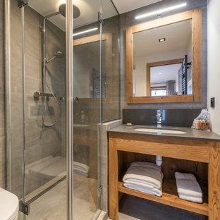 Modelo de cuarto de baño con ducha, rural, de tamaño medio, con armarios abiertos, puertas de armario de madera oscura, ducha esquinera, sanitario de pared, baldosas y/o azulejos grises, paredes blancas, lavabo bajoencimera, suelo gris, ducha con puerta con bisagras y encimeras grises