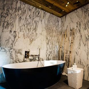 Cette image montre une salle de bain principale bohème de taille moyenne avec une baignoire indépendante et un carrelage gris.