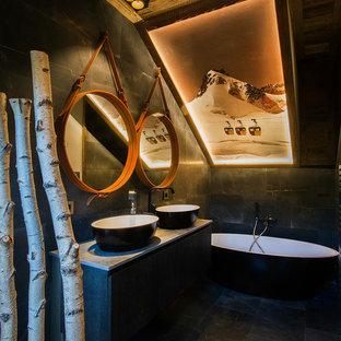 На фото: с высоким бюджетом главные ванные комнаты среднего размера в стиле рустика с черными фасадами, отдельно стоящей ванной, черной плиткой, черными стенами и настольной раковиной