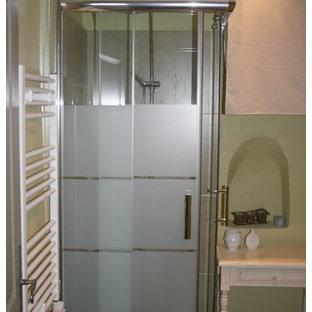 Immagine di una piccola stanza da bagno con doccia mediterranea con doccia ad angolo, WC sospeso, piastrelle verdi, piastrelle di cemento, pareti verdi, pavimento con cementine, lavabo a consolle, pavimento marrone e porta doccia scorrevole