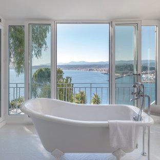 Exemple d'une salle de bain bord de mer avec une baignoire sur pieds et un sol blanc.