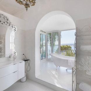 Cette photo montre une salle de bain tendance avec un placard à porte plane, des portes de placard blanches, une baignoire sur pieds, un carrelage blanc, un mur blanc, un lavabo intégré, un sol blanc et un plan de toilette blanc.
