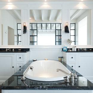 Exemple d'une grand salle de bain principale chic avec un plan de toilette en marbre, une baignoire encastrée, un mur blanc, un sol en bois foncé et un lavabo intégré.