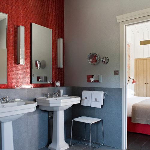 Salle de bain avec un carrelage rouge et un mur gris ...