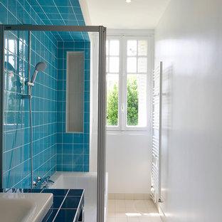 Inspiration pour une salle de bain principale et longue et étroite design avec une baignoire posée, un combiné douche/baignoire, un carrelage bleu, un mur blanc, un lavabo encastré et un plan de toilette en carrelage.