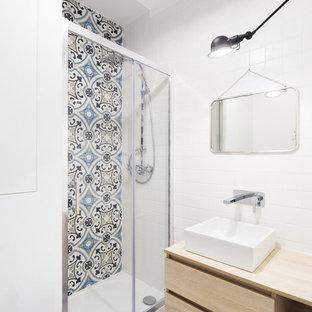 Exemple d'une petit salle d'eau scandinave avec un placard à porte plane, des portes de placard en bois clair, un carrelage bleu, des carreaux de céramique, un mur blanc, un plan vasque et un sol bleu.