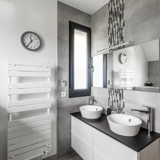 Aménagement d'une salle de bain contemporaine avec un placard à porte plane, des portes de placard blanches, un carrelage gris, un mur blanc, une vasque, un sol gris et un plan de toilette noir.