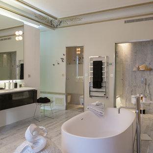 Idée de décoration pour une grande douche en alcôve principale design avec un mur blanc, un placard à porte plane, des portes de placard noires, une baignoire indépendante, un WC suspendu et un lavabo intégré.