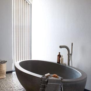 Idées déco pour une grande salle de bain contemporaine avec une baignoire indépendante, un mur blanc, un sol en galet et un sol gris.