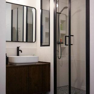 Aménagement d'une petit salle de bain contemporaine avec des portes de placard en bois sombre, un WC suspendu, un carrelage blanc, des carreaux de céramique, un mur blanc, un sol en carrelage de céramique, un plan de toilette en bois, un sol gris, meuble simple vasque, meuble-lavabo sur pied, un placard à porte plane, une vasque, une cabine de douche à porte battante et un plan de toilette marron.