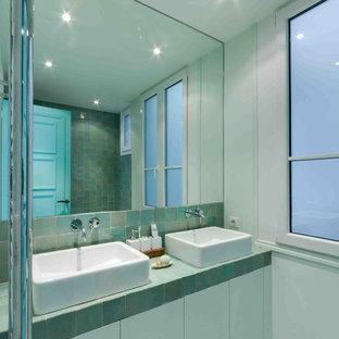 Réalisation d'une salle de bain principale design de taille moyenne avec une vasque, des portes de placards vertess, un carrelage vert et un mur vert.
