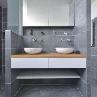 Idée de décoration pour une grand salle d'eau design avec un placard sans porte, des portes de placard blanches, une douche à l'italienne, un carrelage gris, une vasque, un plan de toilette en bois, aucune cabine et un plan de toilette marron.