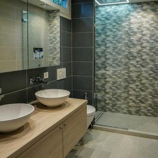 Idée de décoration pour une douche en alcôve principale design avec un carrelage gris, un mur gris, un lavabo suspendu, un sol beige, un plan de toilette beige, un placard à porte plane, des portes de placard beiges, un WC suspendu, des carreaux de porcelaine et un plan de toilette en bois.