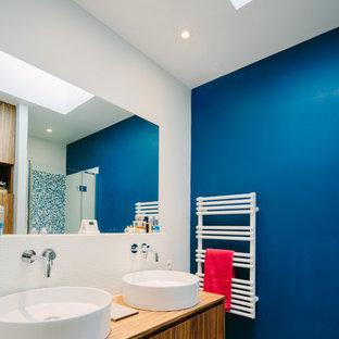 Ejemplo de cuarto de baño con ducha, actual, de tamaño medio, con puertas de armario de madera oscura, baldosas y/o azulejos blancos, paredes azules, lavabo sobreencimera y encimera de madera