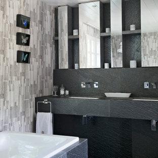 Modelo de cuarto de baño principal, contemporáneo, de tamaño medio, con baldosas y/o azulejos grises, bañera encastrada sin remate, paredes grises y lavabo bajoencimera