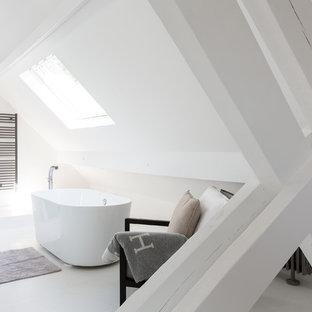Idée de décoration pour une salle de bain principale design de taille moyenne avec une baignoire indépendante et un mur blanc.