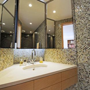 Aménagement d'une salle de bain contemporaine de taille moyenne avec des portes de placard en bois brun, un carrelage beige, un carrelage blanc, un carrelage bleu, un carrelage gris, carrelage en mosaïque et un lavabo encastré.