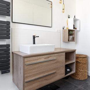 Cette image montre une salle de bain principale design de taille moyenne avec un placard à porte plane, des portes de placard beiges, une baignoire encastrée, un combiné douche/baignoire, un carrelage noir, des carreaux de porcelaine, un mur blanc, un sol en carrelage de céramique, une vasque, un plan de toilette en bois, un sol gris, une cabine de douche à porte battante et un plan de toilette beige.