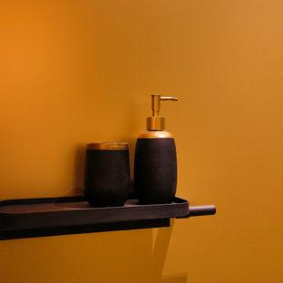 Modelo de cuarto de baño con ducha, tradicional renovado, pequeño, con armarios tipo vitrina, ducha a ras de suelo, baldosas y/o azulejos amarillos, baldosas y/o azulejos de metal, paredes amarillas, suelo de baldosas de cerámica, lavabo integrado, encimera de granito, suelo negro, ducha abierta y encimeras negras
