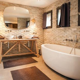 Aménagement d'une salle de bain principale campagne avec un carrelage beige, un sol en carrelage de céramique, un plan de toilette en bois, une baignoire indépendante et une vasque.