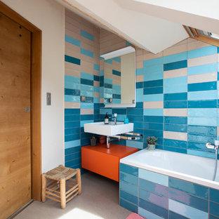 Ispirazione per una stanza da bagno per bambini minimal di medie dimensioni con ante lisce, ante arancioni, vasca sottopiano, WC sospeso, piastrelle blu, piastrelle in ceramica, pavimento in linoleum, lavabo a consolle, top in superficie solida, pavimento grigio, top bianco e pareti blu