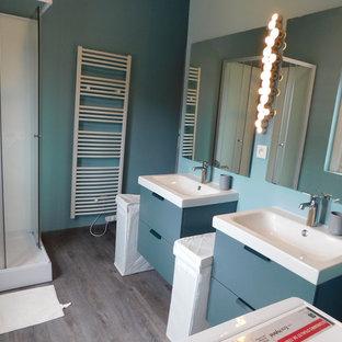 Foto de cuarto de baño principal, moderno, pequeño, con puertas de armario turquesas, paredes azules, lavabo sobreencimera, suelo marrón, ducha con puerta corredera y encimeras blancas