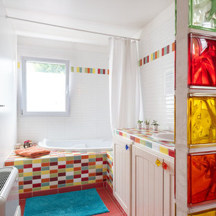 Modelo de cuarto de baño infantil, contemporáneo, de tamaño medio, con bañera esquinera, sanitario de pared, baldosas y/o azulejos multicolor, baldosas y/o azulejos de cemento, paredes blancas, lavabo bajoencimera, encimera de azulejos, suelo rosa y encimeras multicolor