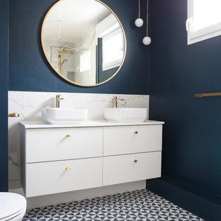 Cette photo montre une grand salle de bain principale tendance avec un placard à porte plane, des portes de placard blanches, un WC suspendu, un carrelage blanc, des carreaux de céramique, un mur bleu, un sol en carrelage de céramique, une vasque, un plan de toilette en surface solide, un sol bleu, une cabine de douche à porte battante, un plan de toilette blanc, meuble double vasque et meuble-lavabo suspendu.
