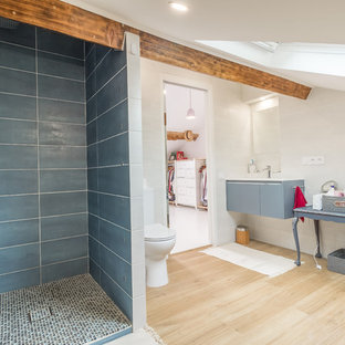 Diseño de cuarto de baño principal, contemporáneo, de tamaño medio, con armarios con paneles lisos, puertas de armario grises, bañera exenta, ducha abierta, sanitario de una pieza, baldosas y/o azulejos blancos, baldosas y/o azulejos de cerámica, paredes blancas, suelo de madera clara, lavabo integrado, encimera de acrílico, suelo amarillo, ducha abierta y encimeras blancas