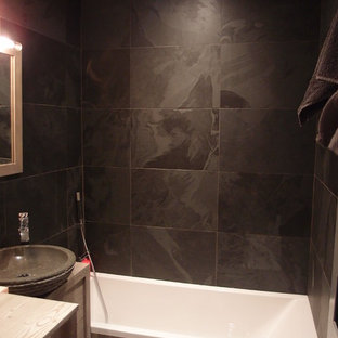 グルノーブルのラスティックスタイルのおしゃれなマスターバスルーム (フラットパネル扉のキャビネット、淡色木目調キャビネット、アンダーマウント型浴槽、黒いタイル、スレートタイル、黒い壁、スレートの床、ベッセル式洗面器、木製洗面台、黒い床、ベージュのカウンター) の写真