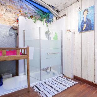Cette image montre une salle d'eau bohème de taille moyenne avec une baignoire encastrée, un combiné douche/baignoire, un mur blanc et un sol en bois brun.
