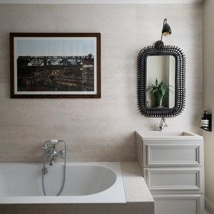 Inspiration pour une salle de bain bohème avec un placard avec porte à panneau encastré, des portes de placard beiges, une baignoire posée, un carrelage beige, un mur beige, un plan vasque et un sol beige.