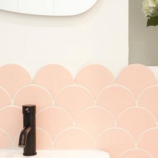 Immagine di una piccola stanza da bagno padronale moderna con ante lisce, ante bianche, doccia alcova, piastrelle rosa, piastrelle in ceramica, pareti bianche, pavimento in cementine, lavabo a bacinella, top in superficie solida, pavimento grigio, WC a due pezzi e top bianco