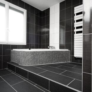 Modernes Badezimmer mit Eckbadewanne, schwarzen Fliesen, schwarzer Wandfarbe und schwarzem Boden in Lyon