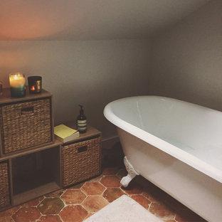 Immagine di una stanza da bagno padronale tradizionale di medie dimensioni con nessun'anta, ante marroni, vasca con piedi a zampa di leone, vasca/doccia, pareti bianche, pavimento in terracotta e pavimento arancione