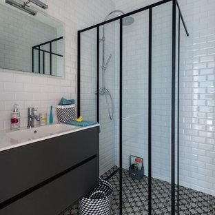 Réalisation d'une salle d'eau urbaine de taille moyenne avec des portes de placard noires, une douche à l'italienne, un mur blanc, un lavabo intégré, un carrelage métro et un carrelage noir et blanc.