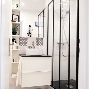 Mid-sized contemporary 3/4 bathroom in Paris with white cabinets, an alcove shower, white tile, black tile, white walls and a vessel sink.