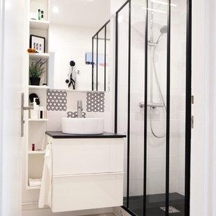 Inspiration pour une salle de bain design de taille moyenne avec des portes de placard blanches, un carrelage blanc, un carrelage noir, un mur blanc et une vasque.