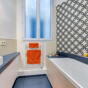 Idée de décoration pour une petit salle d'eau design avec un placard à porte plane, des portes de placard blanches, une baignoire posée, un carrelage beige, un carrelage bleu, des carreaux de porcelaine, un mur blanc, un sol en carrelage de porcelaine, une vasque, un sol bleu et un plan de toilette bleu.