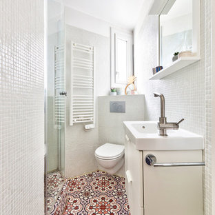 Example of a small trendy master white tile and mosaic tile cement tile floor and pink floor corner shower design in Paris with white walls, white countertops, beaded inset cabinets, white cabinets, a wall-mount toilet, a console sink, solid surface countertops and a hinged shower door