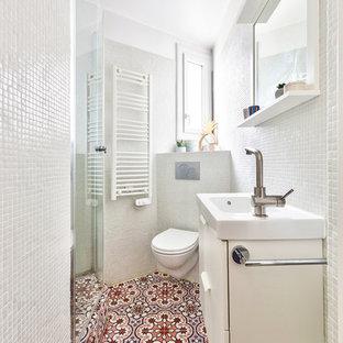 Foto de cuarto de baño principal, actual, pequeño, con baldosas y/o azulejos blancos, paredes blancas, encimeras blancas, armarios con rebordes decorativos, puertas de armario blancas, ducha esquinera, sanitario de pared, baldosas y/o azulejos en mosaico, suelo de azulejos de cemento, lavabo tipo consola, encimera de acrílico, suelo rosa y ducha con puerta con bisagras