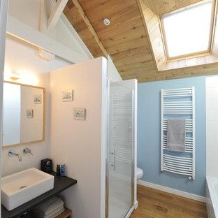 Idée de décoration pour une salle de bain design de taille moyenne avec un placard sans porte, des portes de placard noires, un mur bleu, un sol en bois brun, une vasque et un plan de toilette en bois.