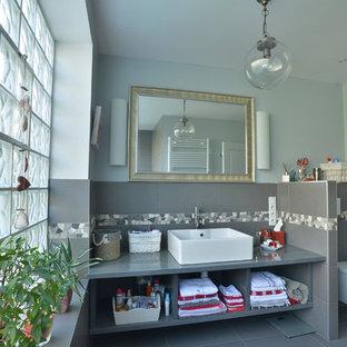 Inspiration pour une salle de bain traditionnelle avec un placard sans porte, des portes de placard grises, un WC suspendu, un carrelage gris, des carreaux de céramique, un mur bleu, un sol en carrelage de céramique et un lavabo posé.
